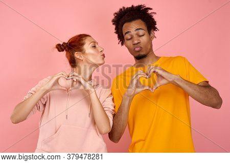 Young Girl Of Caucasian Appearance With A Black Man With Closed Eyes Show His Hands A Heart On A Bac