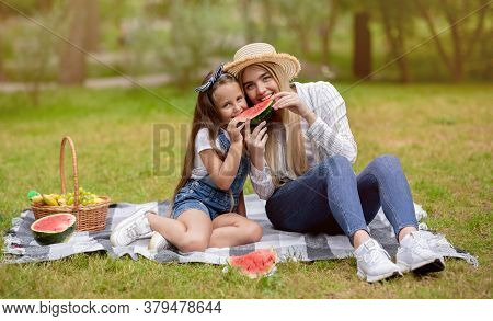 Positive Mom And Daughter Having Picnic Eating Watermelon And Fruits Enjoyng Summer Day In Park Outs