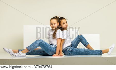 Two Little Girls Posing In The Studio On White Cubes. The Concept Of Tenderness And Beauty.