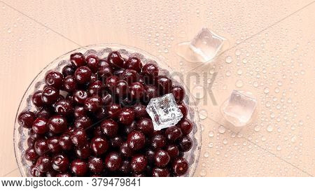 Ripe Cherries In Glass Dish On The Table In Drops Of Water And With Ice Cubes On The Surface. Fresh