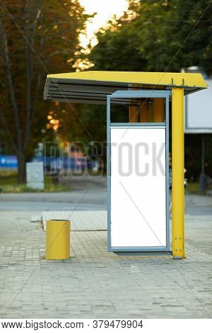 Empty Billboard At Tram Stop. White Vertical Mockup On The Bus Stop. Outdoor Advertising