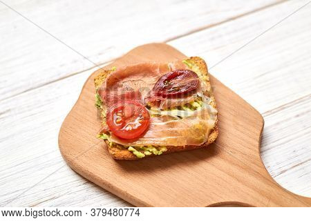 Ciabatta With Jamon, Prosciutto And Avocado With Tomato And Vegetables On A White Background. Health
