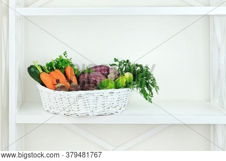 Autumn Vegetables In Basket On Shelf In Wooden Rack Near A White Wall. Empty Space For Putting Text.
