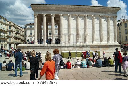 Nimes France. View Of The Beautiful Maison Carree, An Intact Roman Temple. People Walk By On A Summe