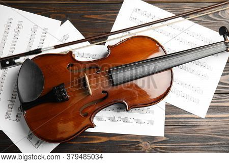 Beautiful Violin, Bow And Note Sheets On Wooden Table, Flat Lay
