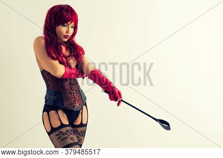 Dominant Woman In A Red Wig Corset And Leather Gloves Posing On A White Background. Mistress Holds A