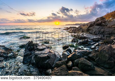 Beach Of The Sea At Sunset. Wonderful Scenery With Stones In The Water. Beautiful Clouds Above The S