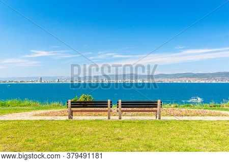 Two Benches On The Sunny Beach Shore. Beautiful View From Paved Footpath On The Seaside. City And Mo