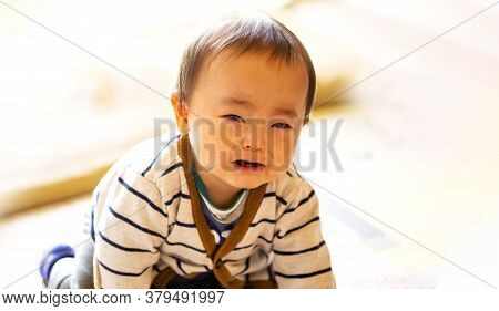 Crying Infant Baby Boy Crawling To The Camera On The Floor And Copy Space.
