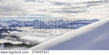 Snow Covered Mountains With Inversion Valley Fog And Trees Shrouded In Mist. Panoramic Snowy Winter