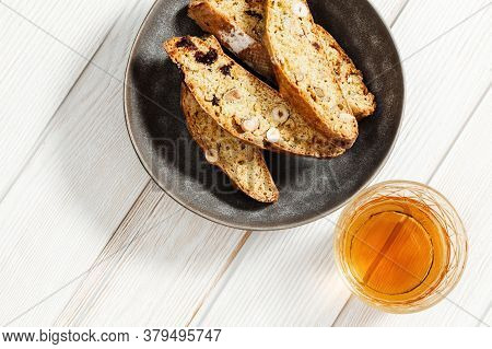 Italian Biscotti Cookies In Grey Plate And Sweet Wine Vin Santo. Fresh Baked Cookies With Nuts And D
