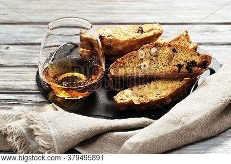 Italian Biscotti Cookies On Black Slate Board And Sweet Wine Vin Santo. Fresh Baked Cookies With Nut