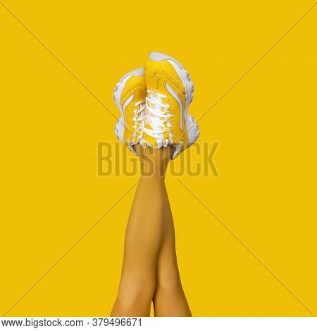 New Yellow Female Sneakers On Long Slender Woman Legs In Yellow Tights Isolated On Yellow Background