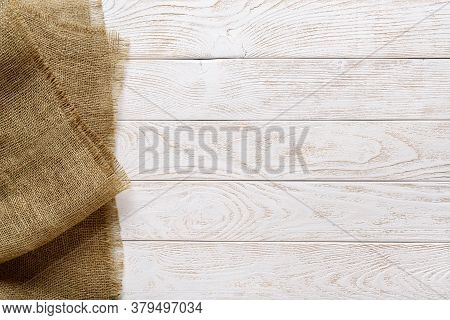 Copy Space On A Rustic Textured Wood Tabletop Painted With White Paint And Burlap Of Natural Color O