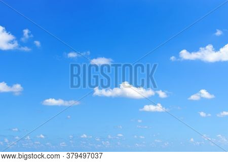 Sparse Small White Fluffy Clouds Float Slowly High In The Bright Blue Summer Sky On A Sunny Day. Con