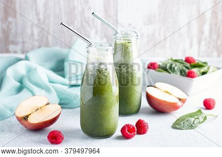 Two Glass Bottles Of Green Smoothie With Spinach, Raspberry And Apple On Concrete Table, Still Life.