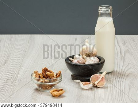 Health Remedy Relief Foods And Drink For Cold And Flu With Garlic, Yogurt And Walnuts On Wood Boards