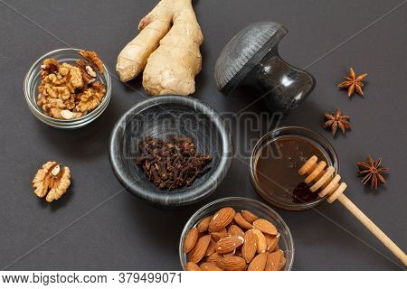Health Remedy Foods For Cold And Flu Relief With Ginger, Honey, Almond And Walnuts On A Black Backgr
