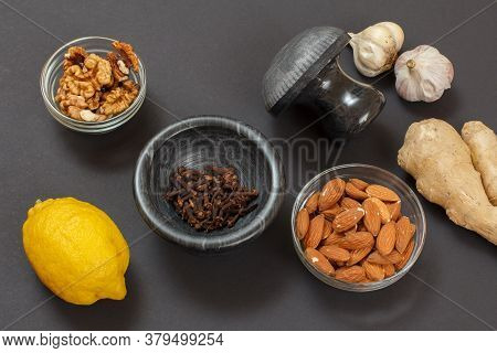 Health Remedy Foods For Cold And Flu Relief With Lemon, Garlic, Ginger, Almond And Walnuts On A Blac