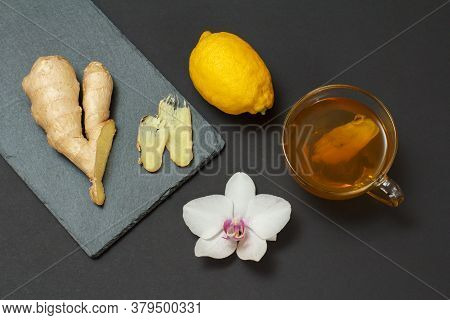 Health Remedy Foods For Cold And Flu Relief With Lemon, Ginger And Tea On A Black Background. Top Vi