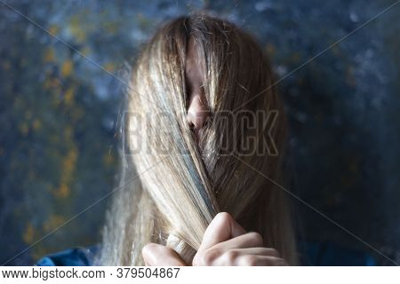 Portrait Of A Blonde Pulling Her Hair Over Her Face. On A Dark Background. The Concept Of Depression