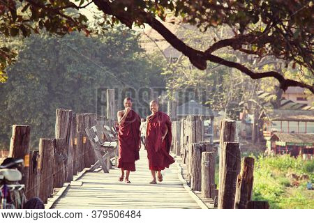 AMARAPURA, MYANMAR - CIRCA FEBRUARY 2018: Monks walk along famous teak U-Bein bridge in Amarapura, Mandalay, Myanmar. Ancient U-Bein bridge in the Mandalay region is the popular toutist attraction.