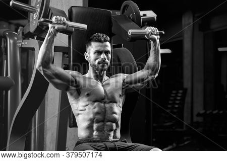 Monochrome Close Up Of Young Muscular Man On Simulator In Gym. Fit Shirtless Bodybuilder With Perfec