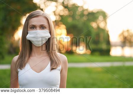 Portrait Of Young Attractive Woman Wearing White Protective Face Mask Looking At Camera. Pretty Fema