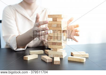 Businessmen carefully placed wooden blocks in a high tower, Protecting a tall wooden tower also invo