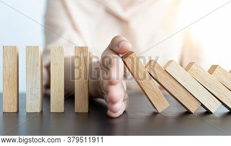 Businesswoman stops hands falling over domino to stop risk continuously, Continuous damage reduction