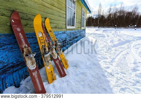 Ruka, Finland - February 24, 2018: Red And Yellow Old Fashioned Wooden Skis Standing Near Old House