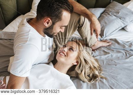 Image of a young optimistic positive loving couple lying on a bed in bedroom indoors at home