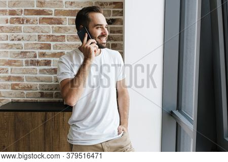Image of a young happy optimistic man indoors at home talking by smartphone
