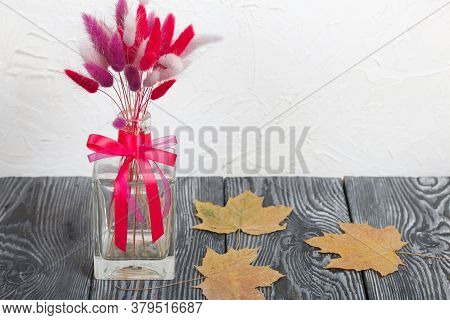A Bouquet Of Dried Flowers In A Glass Bottle. Nearby Are Dried Maple Leaves. On A White Background.