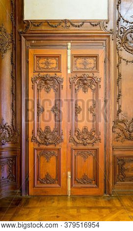 Closed Elegant Lumber Door With Engraved Decorations, Installed In Wooden Ornamental Archway Leading