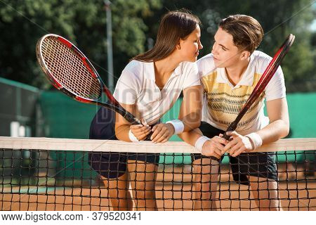 Young Couple Flirting With Each Other While Standing On The Tennis Court After The Game
