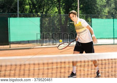 Young Tennis Player Hitting The Ball. Sporty Man