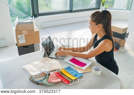Online small business entrepreneur woman working remote from home on laptop selling cloth mask handmade from fabric on ecommerce app for COVID-19.