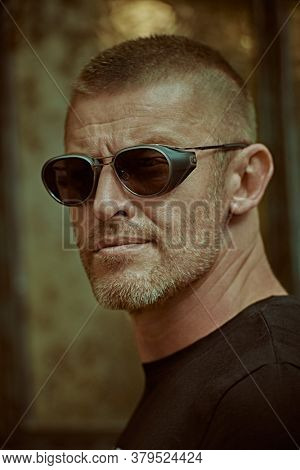 Close-up portrait of a handsome brutal mature man with short hair and bristles wearing trendy sunglasses. Manly style. Optics for men.