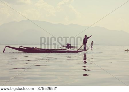INLE LAKE, MYANMAR - CIRCA FEBRUARY 2018: Inle lake fishermen is practicing a special paddling style and fishing tool on the Inle lake, Myanmar.