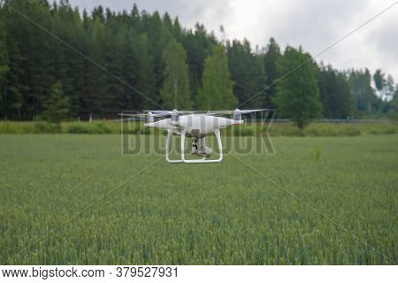 Leningrad Region, Russia - July 21, 2018: Quadrocopter Flies Over A Green Field On A Cloudy Summer D