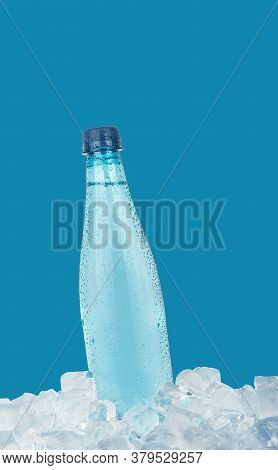 One Full Pet Plastic Bottle Of Cold Still Drinking Water Chilling On Ice Cubes Isolated On Blue Back