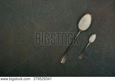 Close Up Flat Lay Two Vintage Metal Spoons Of White Sugar And Sea Salt On Dark Grunge Stone Table Su