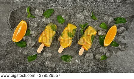 Close Up Three Fruit Ice Cream Popsicles With Fresh Orange Slices, Green Mint Leaves And Ice Cubes O