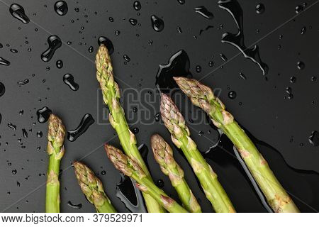 Close Up Bunch Of Washed Fresh Green Asparagus On Black Table With Drops Of Water, Elevated Top View