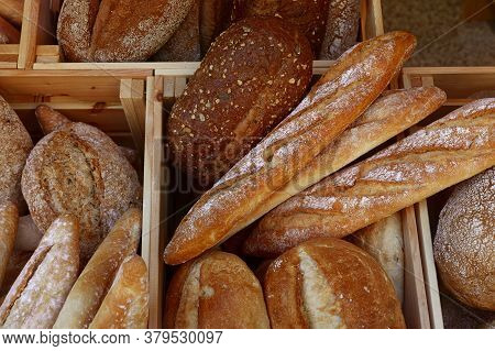 Close Up Several Assorted Fresh Wheat Bread Loaves And Baguettes In Wooden Box On Retail Display Of