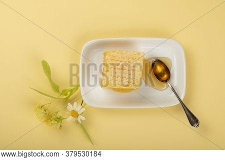 Close Up Fresh Acacia Honey With Honeycomb, Spoon, Linden And Chamomile Flowers On White Plate Over