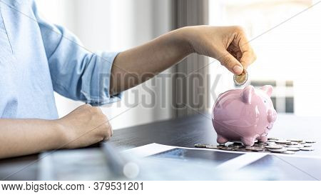 Businessman's hand holds the money in the piggy bank for saving money for future use, saving money f