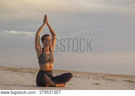 Active Young Woman Enjoying Beautiful Sunrise On The Beach, Relaxing By Practising Yoga, Doing Cross