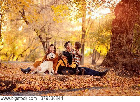 Family With Two Daughters And A Labrador Retriever Sitting In The Autumn Park. Children And Pets.
